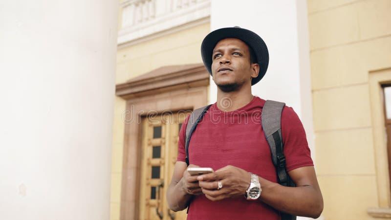 Lächelnder touristischer Mann des Afroamerikaners, der Smartphoneon-line-Karte verwendet, um richtige Richtungen zu finden, an de stockfotografie
