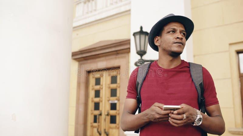 Lächelnder touristischer Mann des Afroamerikaners, der Smartphoneon-line-Karte verwendet, um richtige Richtungen zu finden, an de lizenzfreie stockfotografie