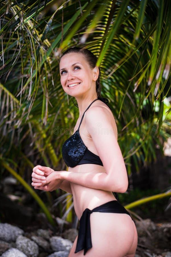 Lächelnder tragender Bikini des nahen hohen Porträts der Frau, der auf dem Strand an einem sonnigen Tag sich entspannt lizenzfreie stockfotos