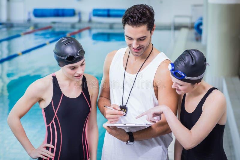 Lächelnder Trainer, der Klemmbrett an den Schwimmern zeigt stockbild