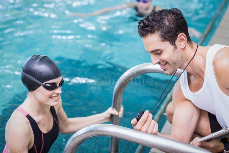 Lächelnder Trainer, der Stoppuhr am Schwimmer zeigt lizenzfreie stockbilder
