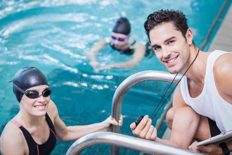 Lächelnder Trainer, der Stoppuhr am Schwimmer zeigt lizenzfreies stockbild