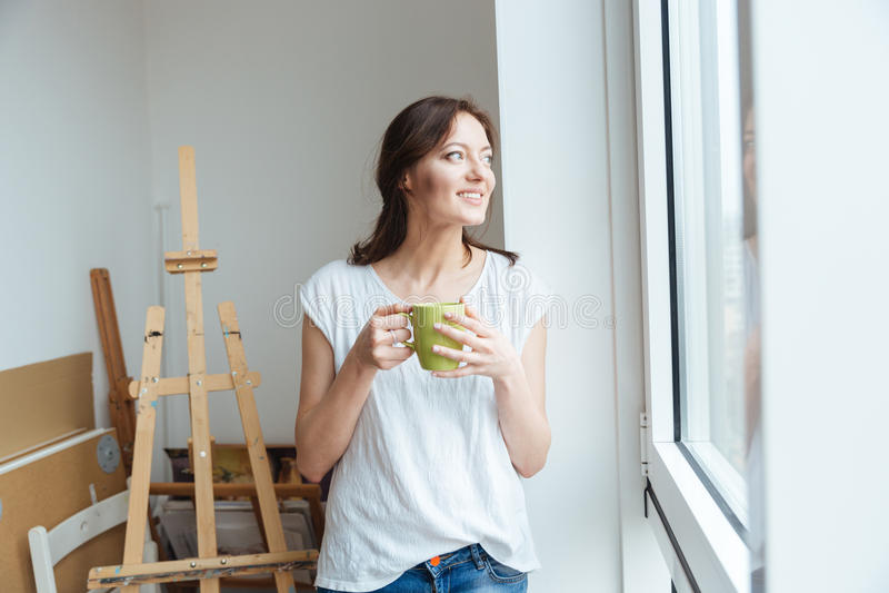 Lächelnder trinkender Kaffee der hübschen Künstlerin in der Werkstatt stockbilder