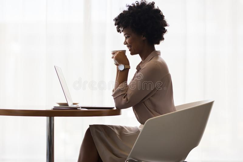 Lächelnder trinkender Kaffee und Anwendung der Geschäftsfrau des Laptops stockbild
