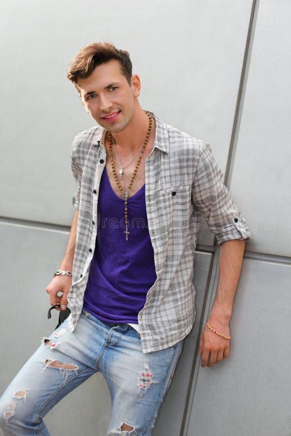 Lächelnder ungewöhnlicher Mann, der zerrissene Jeansstandplätze trägt lizenzfreie stockfotografie