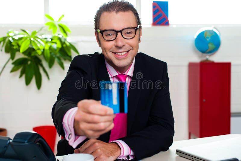Lächelnder Unternehmensleiter, der Kreditkarte anzeigt lizenzfreie stockfotos