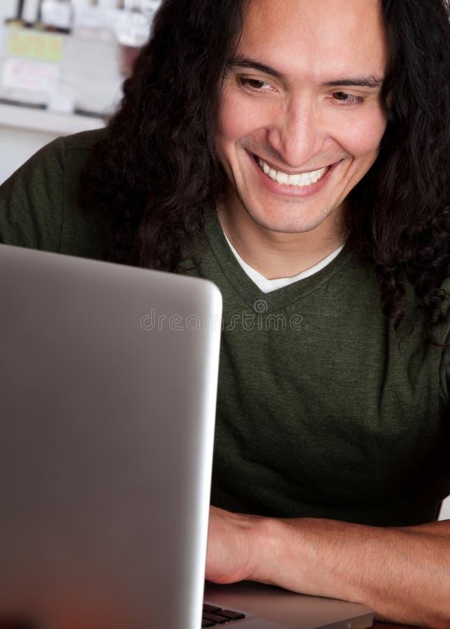 Lächelnder Ureinwohner-Mann, der an einem Laptop arbeitet stockbilder