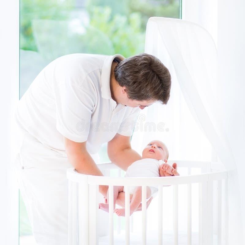 Lächelnder Vater, der sein neugeborenes Baby in Krippe einsetzt stockbild