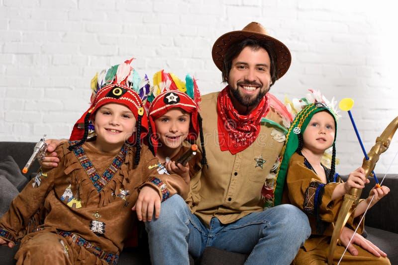 lächelnder Vater im Hut und in rotem Bandana, die auf Sofa mit kleinen Söhnen in den einheimischen Kostümen sitzen lizenzfreie stockfotografie