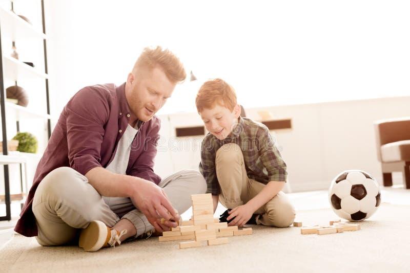 lächelnder Vater und Sohn, die mit Holzklötzen spielen lizenzfreie stockbilder