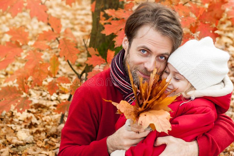 Lächelnder Vater und Tochter, die den Spaß im Freien im Herbst hat stockfotos