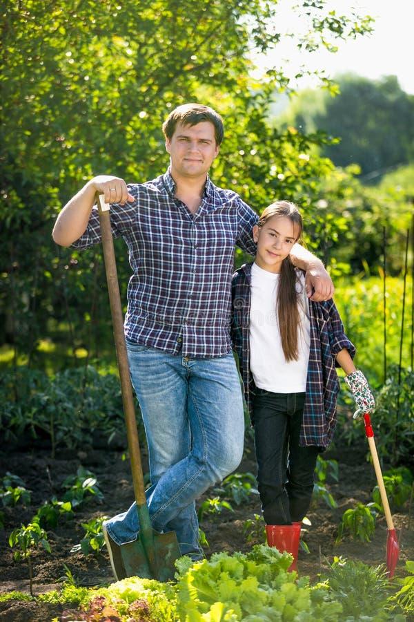 Lächelnder Vater und Tochter, die am Garten mit Schaufeln aufwerfen stockfotos