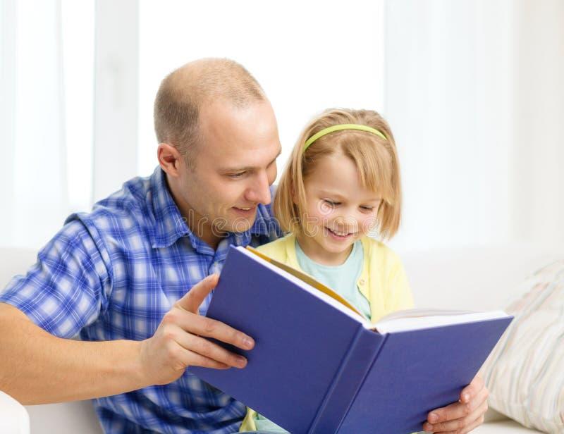 Lächelnder Vater und Tochter mit Buch zu Hause lizenzfreie stockbilder