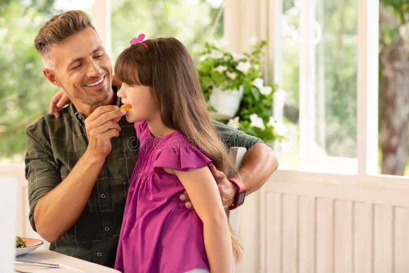 Lächelnder Vati beim Geben seines netten Tochterstückes der Süßigkeit lizenzfreies stockfoto