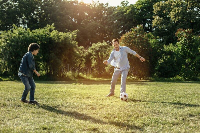 Lächelnder Vati und Junge, die Fußball spielen lizenzfreies stockfoto