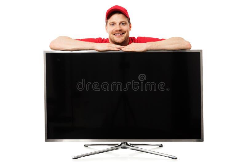 lächelnder Verkäufer in der roten Uniform über großem Schirm des freien Raumes Fernseh lizenzfreie stockfotos