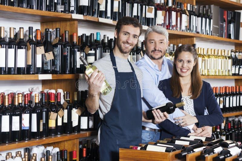 Lächelnder Verkäufer Holding Wine Bottles während Paare, die in S stehen stockbild