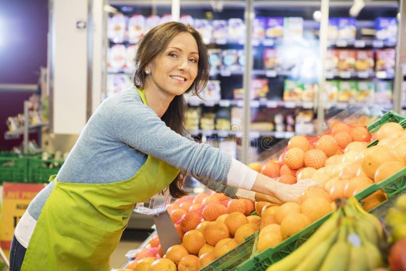 Lächelnder Verkäuferin-Arranging Oranges In-Supermarkt stockfotografie
