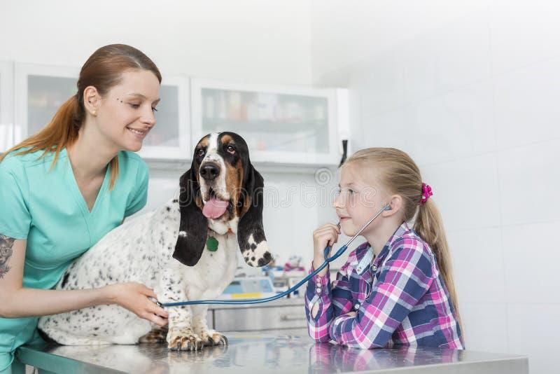 Lächelnder Veterinärdoktor, der Hund während Mädchen hört durch Stethoskop an der Klinik hält lizenzfreie stockbilder