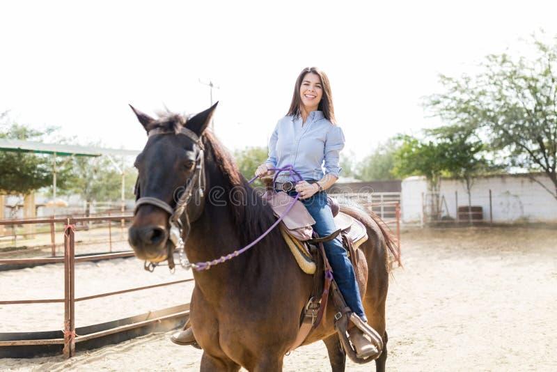 Lächelnder Viehzüchter beim Reiten von Brown-Pferd lizenzfreie stockbilder