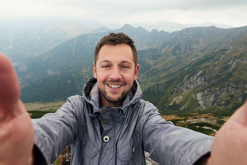 Lächelnder Wanderer, der ein selfie vor Berglandschaft nimmt stockbild