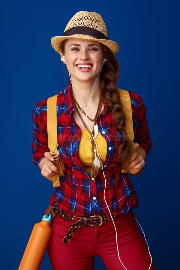 Lächelnder Wanderer der jungen Frau mit Kopfhörern hörend Musik stockfotografie