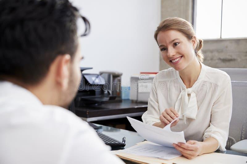 Lächelnder weißer weiblicher Fachmann in der Sitzung mit jungem Mann stockfotografie