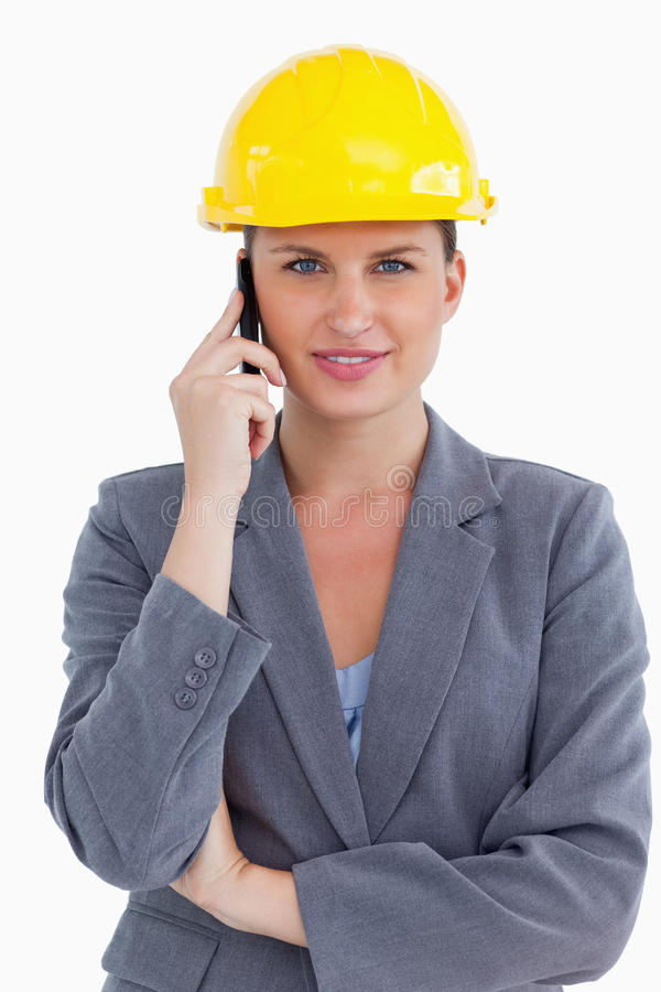 Lächelnder weiblicher Architekt auf ihrem Mobiltelefon stockbild