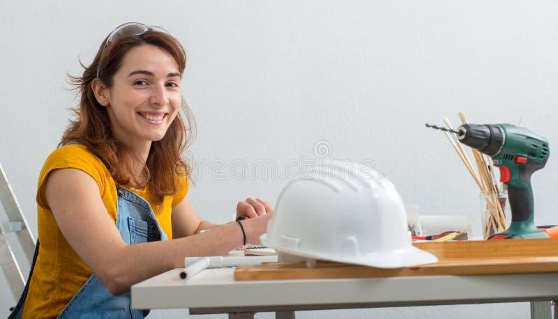 Lächelnder weiblicher Architekt der Junge im Büro stockfoto