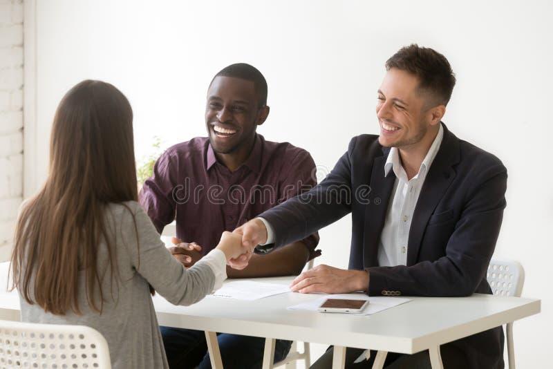 Lächelnder weiblicher Bewerber Stunden-Händeschüttelns am Vorstellungsgespräch, stellend an stockfotografie