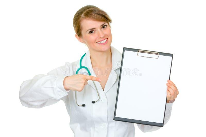 Lächelnder weiblicher Doktor, der auf unbelegtes Klemmbrett zeigt lizenzfreie stockbilder