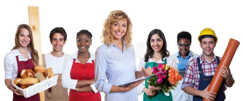 Lächelnder weiblicher Geschäftsauszubildender mit Gruppe anderer internationaler Lehrlinge stockfoto