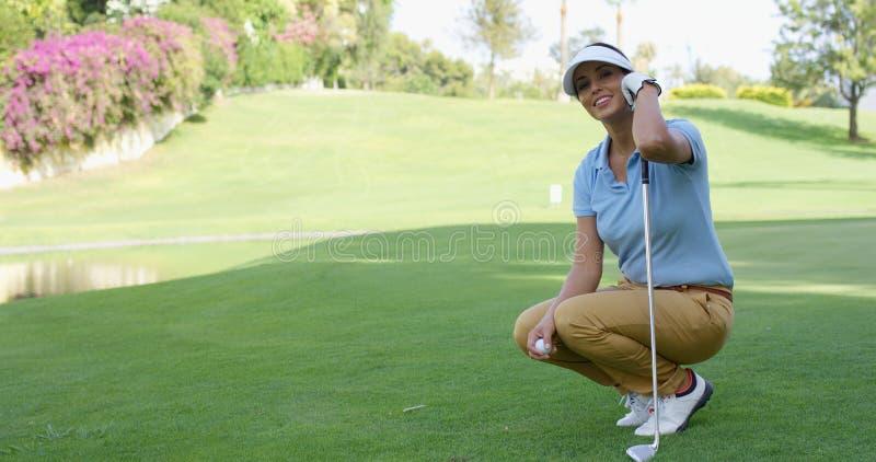 Lächelnder weiblicher Golfspieler mit dem braunen Haar duckt sich stockbild