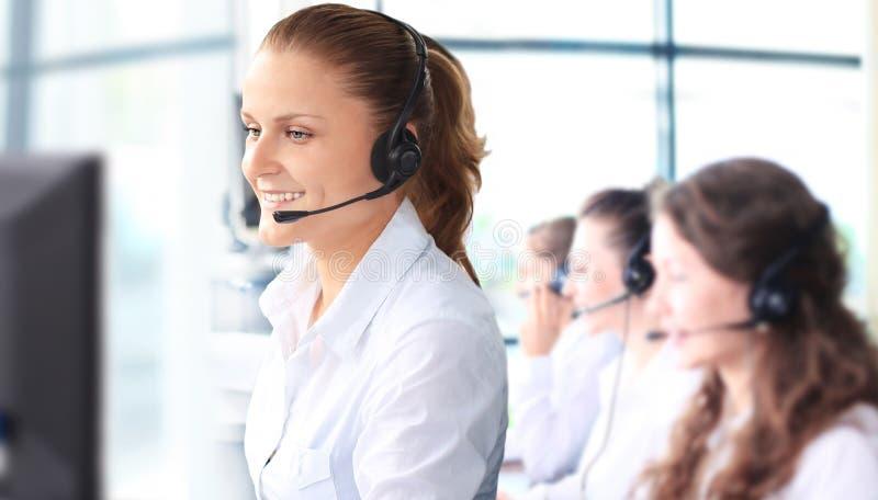 Lächelnder weiblicher Kundendienstmitarbeiter, der auf Kopfhörer spricht stockfotografie