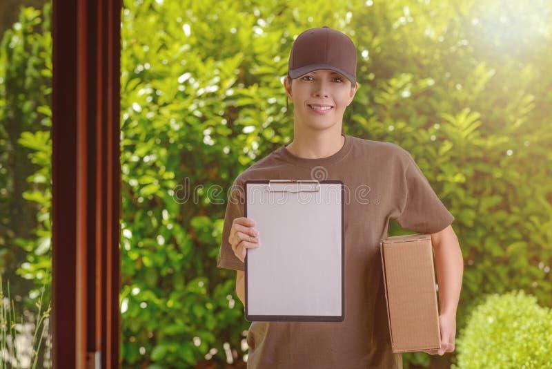 Lächelnder weiblicher Kurier, der ein Paket liefert lizenzfreie stockfotos