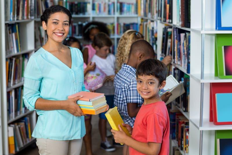 Lächelnder weiblicher Lehrer, der dem Jungen Bücher gibt lizenzfreie stockfotografie