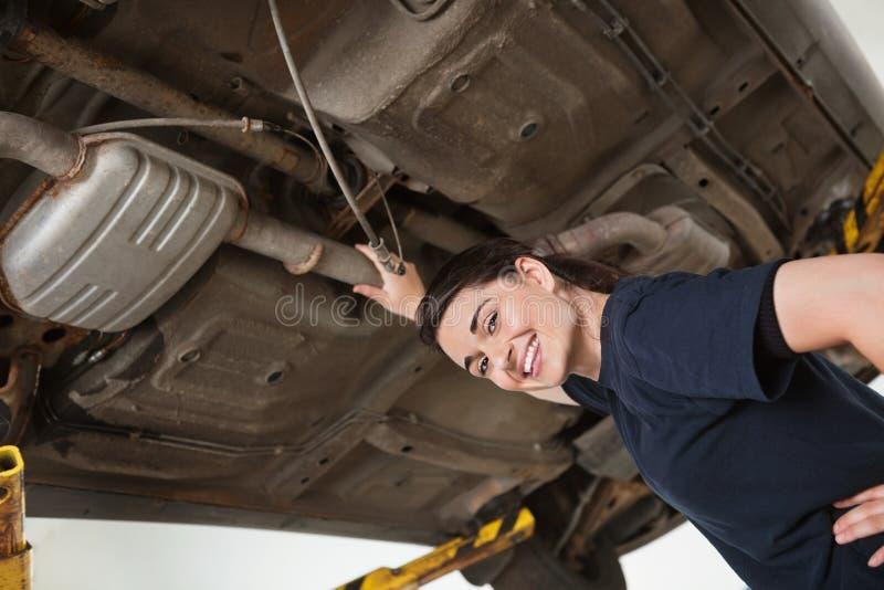Lächelnder weiblicher Mechaniker unter Auto lizenzfreies stockbild