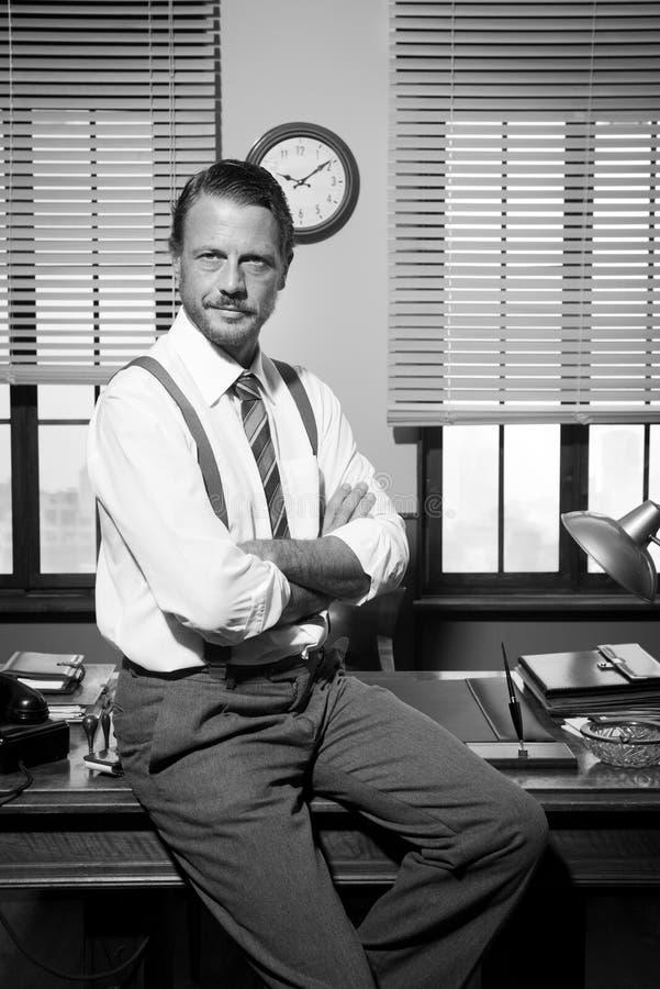 Lächelnder Weinlesegeschäftsmann, der auf Schreibtisch sitzt lizenzfreie stockfotografie