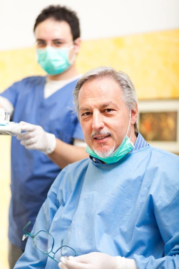 Lächelnder Zahnarzt mit seinem Assistenten stockfotografie