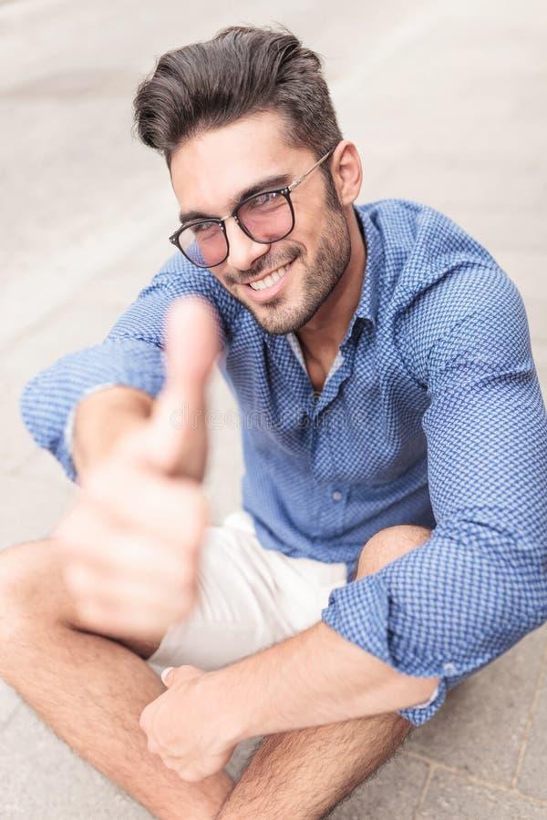Lächelnder zufälliger Sitzmann, der das okayzeichen macht lizenzfreies stockbild