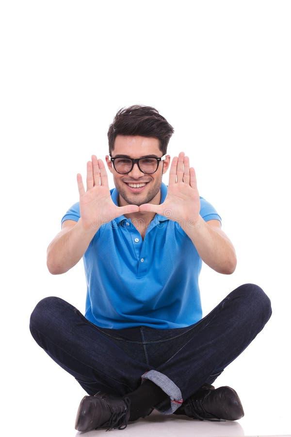 Lächelnder zufälliger Sitzmann, der einen Handrahmen macht stockfotografie