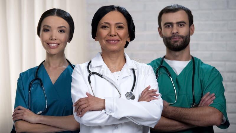 Lächelndes Ärzteteam bereit zu den Operationen, geduldige Behandlung in den sicheren Händen stockfoto