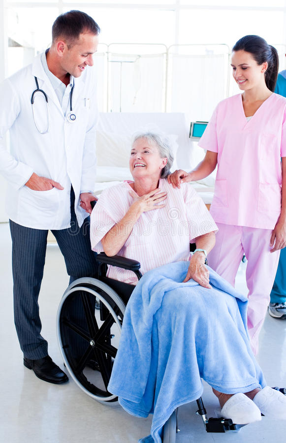 Lächelndes Ärzteteam, das um einer älteren Frau sich kümmert lizenzfreies stockbild