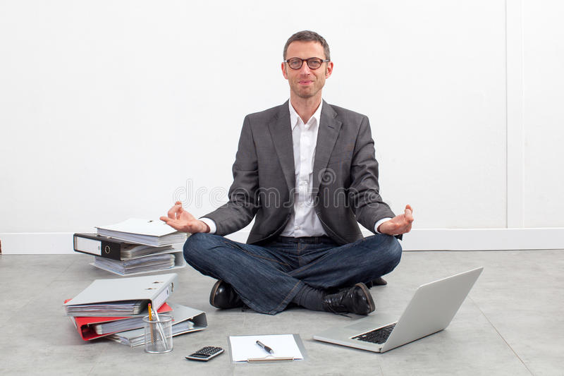 Lächelndes übendes Yoga des Geschäftsmannes im Büro für Entspannung stockbild