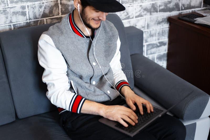 Lächelndes Arbeiten des jungen Mannes an Laptop auf dem Sofa lizenzfreies stockbild