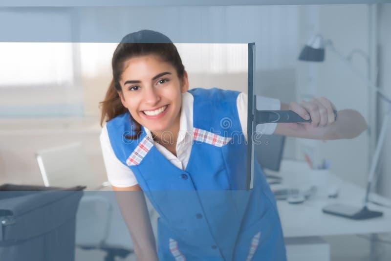 Lächelndes Arbeitnehmerin-Reinigungsglasfenster mit Gummiwalze stockfoto