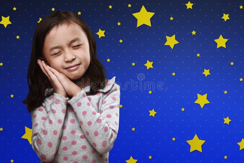 Lächelndes asiatisches kleines Mädchen stützen zu ihren Händen unter ihren Kopf stockfoto