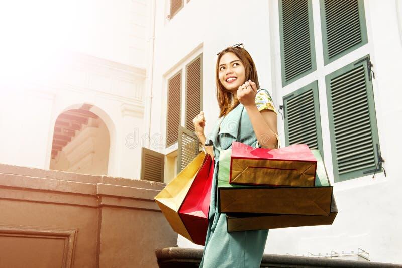 Lächelndes asiatisches Mädchen, das den Einkauf mit Einkaufstaschen in ihrem h genießt lizenzfreie stockfotos
