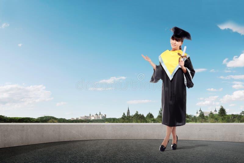 Lächelndes asiatisches Mädchen in der Staffelung bedecken und in der Diplomrolle mit einer Kappe stockfotografie