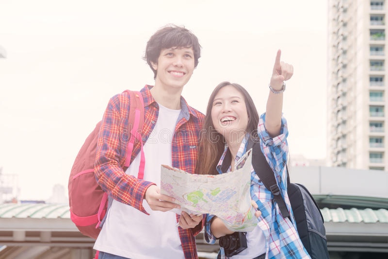Lächelndes asiatisches Mädchen des Ferien- und Freundschaftskonzeptes und fremde Freunde mit Stadtführerkarte und -rucksack in de stockbild